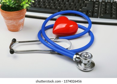 Stethoscope on modern laptop computer. red heart on white table with space for text. Healthcare concept