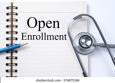 Stethoscope on notebook and pencil with Open Enrollment words as medical concept.