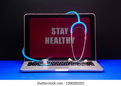 A stethoscope on a silver laptop with black and blue background.