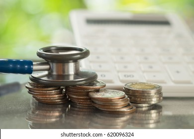 Stethoscope on stack of coins with calculator, concept of Financial Health