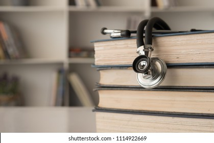 stethoscope on stack of medical guide book for doctor learning treatment at hospital.
