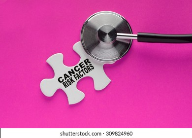 Stethoscope on top of a white jigsaw puzzle with a written word cancer risk factors on a pink background. Cancer awareness campaign concept.