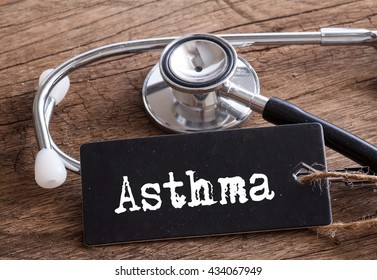 Stethoscope on wood with Asthma word as medical concept