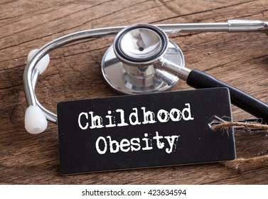 Stethoscope on wood with Childhood Obesity word as medical concept