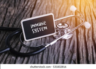 Stethoscope on wood with immune system word as medical concept.