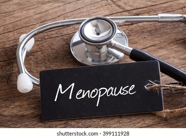 Stethoscope on wood with Menopause word as medical concept