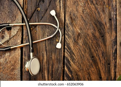 Stethoscope on wooden background.