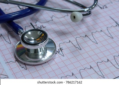 Stethoscope and paper of ekg graph on wood table