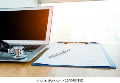Stethoscope, pen, laptop and blank prescription form on doctor working table.