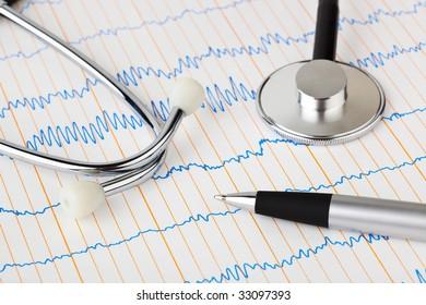 Stethoscope and pen on ecg - medical background