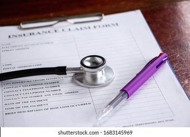 The stethoscope and pen put on blurred Insurance claim form,blurry light around