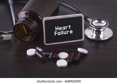 Stethoscope, pill bottle, Various pills, capsules and Heart Failure on wooden background with copyspace area.