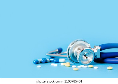 Stethoscope and pills on blue background copy space