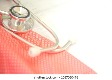 Stethoscope and pink fabric on white wood background. Healthcare , Medical concept. Hypertension day. Copy space.