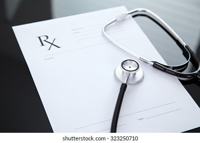 Stethoscope and prescription, black reflective background