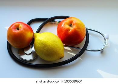 Stethoscope, red apples, lemon, white background