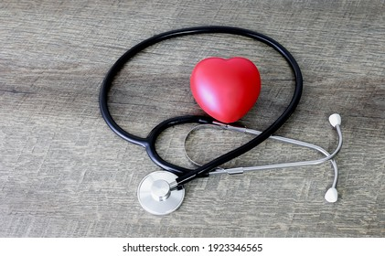 Stethoscope and red heart on old wooden table background. Healthcare concept.