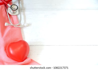Stethoscope and red heart on pink fabric. White wood background. Health care / Medical concept. Copy space. Can be use for brochure, advertising, hypertension day.