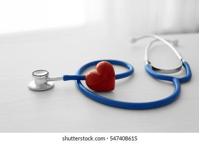 Stethoscope and red heart on table