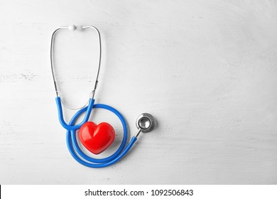 Stethoscope and red heart on white wooden background. Health care concept