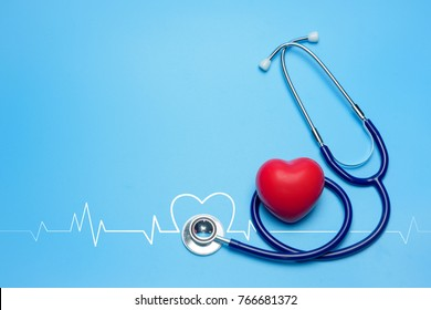 Stethoscope and red heart shape with cardiogram on blue background, Heart and health care concept