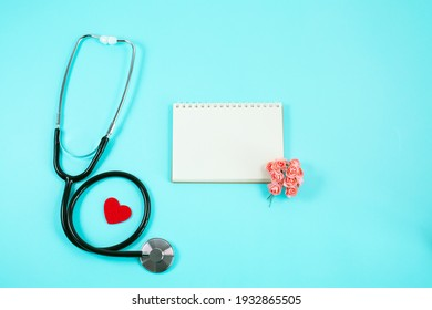 Stethoscope with Red heart, small flowers and notebook on blue background. Copy space.