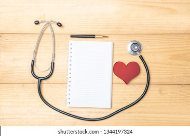 Stethoscope and red heart with white papers and pen on the wooden table. Health day concept