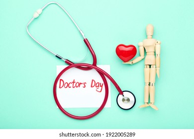 Stethoscope with red heart, wooden figure and text Doctor's Day on mint background