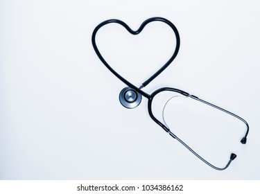 Stethoscope in the shape of heart on white background.