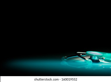 Stethoscope in a spotlight on blue reflective table and black background