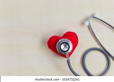 Stethoscope with Strong red heart on wood table on doctor desk with copy space. Check up health for buy insurance concept.