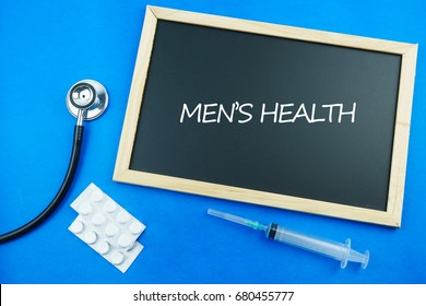 Stethoscope, syringe and medications and a chalkboard with text men's health. Men's health refers to a state of complete physical, mental, and social well-being, as experienced by men.