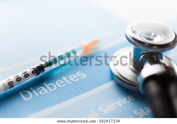 Stethoscope and a syringe on a diabetes test
