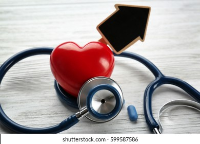 Stethoscope and tag in shape of house on wooden background