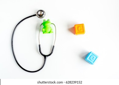 stethoscope, toys on children's doctor office desk background top view mockup