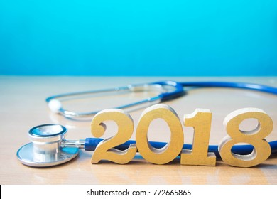 Stethoscope w/ 2018 gold wood number on doctor desk blue background. Happy New Year for healthcare and medical. Creative idea for new trend in medicine treatment and diagnosis concept. Copy space.
