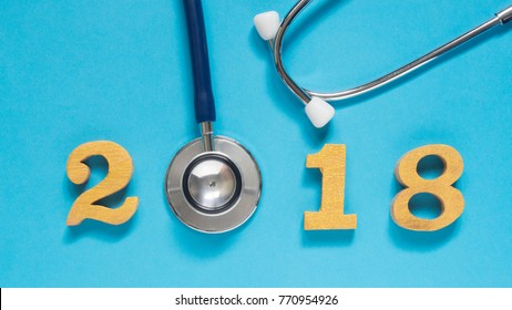 Stethoscope w/ 2018 gold wooden number on blue background. Happy New Year for healthcare and medical banner/calendar cover. Creative idea for new trend in medicine treatment and diagnosis concept.