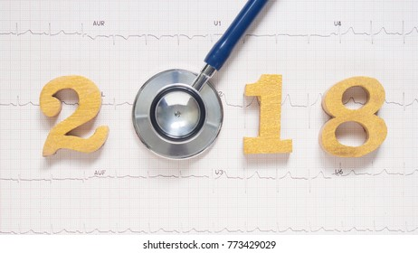 Stethoscope w/ 2018 gold wooden number on ECG background. Creative idea for new trend in medicine treatment and diagnosis concept. Happy New Year for healthcare and medical banner/calendar cover.