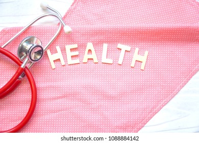 Stethoscope and word health on pink fabric. White wood background. Health care / Medical concept. Copy space. Can be use for brochure, advertising.