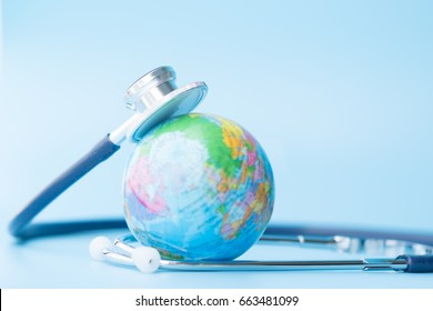 Stethoscope wrapped around globe on blue background. Save the wold, Global healthcare and Green Earth day concept.
