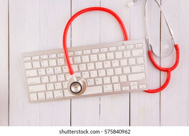 Stethoscope,computer keyboard on wooden desk as medical concept