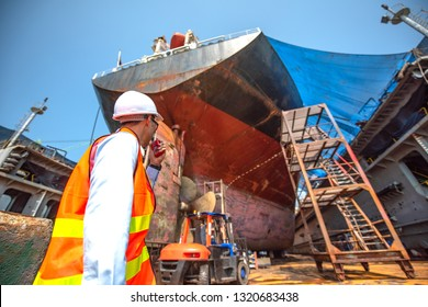 Stevedore, controller, Port Master, surveyor inspect the aft stern of commercial cargo ship in floating dry dock, recondition of overhaul repairing and painting, sand blasting in dry dock yard