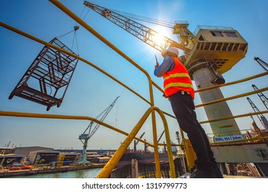 stevedore or foreman, engineering, loading master talks to crane driver by walkie talkie for safety lifting  the goods or shipment, lifting by gantry crane, working at risk on the high level insurance