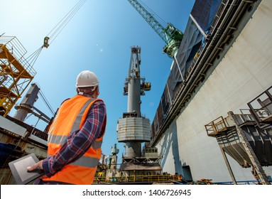 stevedore or foreman, engineering, loading master talks to crane driver by walkie talkie for safety lifting the goods shipment, lifting by gantry crane, working at risk on the high level insurance