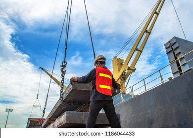 stevedore labor working on plate of steel slab lifting by the ship crane, loading discharging operation for transfer the cargo shipment in export and import, works by stevedore labor on port terminal