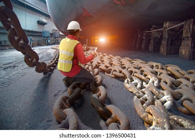 Stevedore, port controller, Port Master, surveyor inspect under bottom hull chains bundle of commercial ship in dry dock yard, recondition of overhaul repairing and repainting, working in dry dock