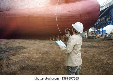 Stevedore, port controller, Port Master, surveyor inspect the bulk head of commercial cargo ship in floating dry dock yard, recondition of overhaul repairing and repainting, working in dry dock yard