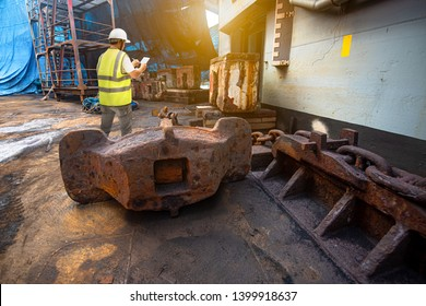 Stevedore, port controller, Port Master, surveyor inspect anchor and chain condition cargo ship in floating dry dock yard, recondition of overhaul repairing and repainting, working in dry dock yard