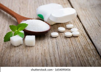 Stevia leaf and white sugar in wooden spoon with sweetener tablets on wood table background. sweetener plant concept.