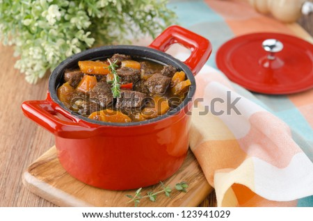 stew of beef with vegetables and prunes in a red cast iron pan